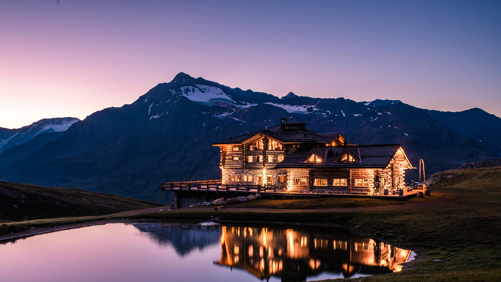 The mountain lodge at night illuminated by lights near the natural park of Stelvio